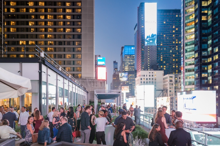 Guests enjoying the extravagant views of New York City's evening skyline. Photography by Erik Bardin.